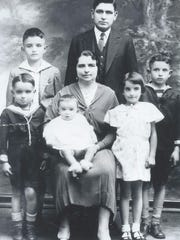 George Cominos, front left. Seated is  Helen Cominos, with Andy in lap; Sophia Cominos to her right;  Nick Cominos  is behind George; At top, Harry Cominos with Ted Cominos to his right.