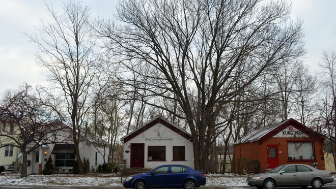 Three brick cottages, dating to the mid-1800s, stand in the 600 block of South Dubuque Street in what was once Iowa City's rail district. The cottages could be demolished under a proposed residential and retail development project for the block.