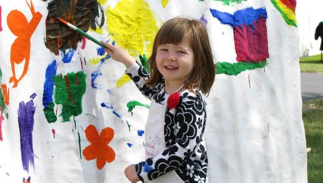 A child exercises her creative abilities on the traditional 50-foot-long mural that the public paints at last year's Sturgeon Bay Fine Art Fair.