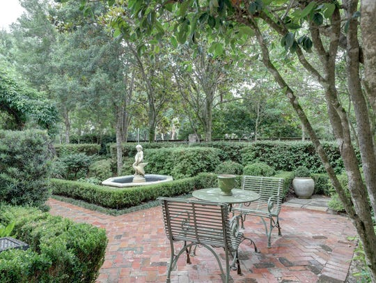 The backyard features manicured green spaces and formal