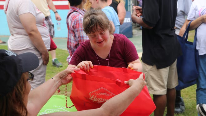 In this file photo from July 2018, Sarah Reo grabs a bag of goodies at East Fishkill's A Day at the Beach at Red Wing Park. The park is one of five in Dutchess receiving grants to fund improvements to make parks more accessible.