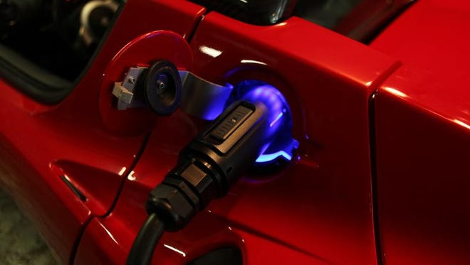 The connection plug glows on Anne Sumers' Tesla roadster, photographed at her Cortlandt Manor home Oct. 11, 2013. She uses it daily to commute to her office in Ridgefield, N.J.
