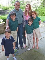 Baher Malek, center, and his wife Bess Malek, stand with their children (from left) Theodore Atticus, 4; Benjamin, 9; Zachary, 7; and Clara, 11, at their home, Tuesday, May 7, 2015.
