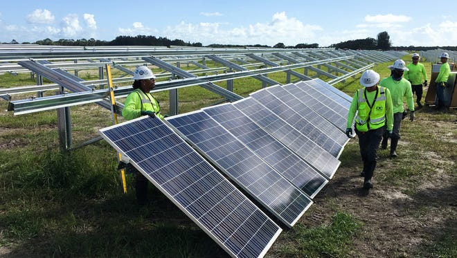 Workers prepare solar panels to be installed at the new Florida Power and Light plant in Barefoot Bay.