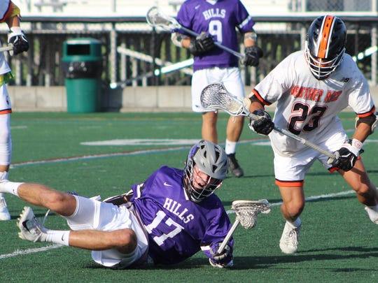 Bloomfield Hills junior Isaac Leader (17) continues to cradle the ball on the turf as Rice midfielder Connor Marsh (23) moves in for the steal.