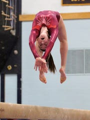 Lexie Cody of CVU does a backflip on the beam during the 2017 Gymnastics state championships at Essex High School.