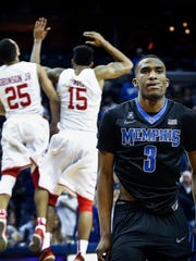Dejected University of Memphis guard Jeremiah Martin (right) walks off the court as University of Houston teammates Galen Robinson Jr. (left) and Devin Davis (middle) celebrate a 72-71 victory at the FedExForum Sunday.
