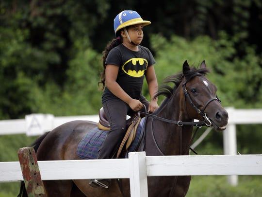 Work to Ride participant Marisol Jimenez, 9, rides a pony named Lyric in Philadelphia.