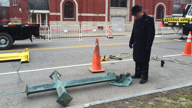 The Rev. Matthew Jones, parochial vicar at St. Mary's R.C. Church in Rochester, stands over the cross that wind brought down after 77 years.