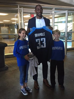 Titans marketing coordinator Toks Sokoya presented Baylor Bramble's siblings, Macy and Brady, a Titans jersey and a signed mini-helmet Tuesday.