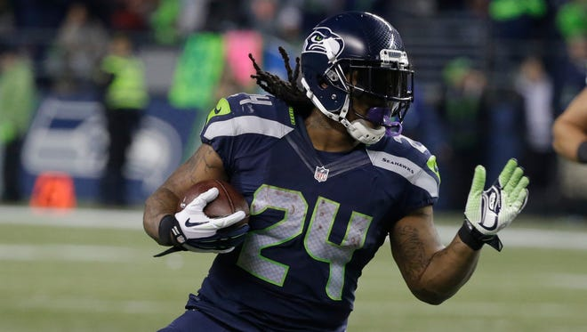 Seattle Seahawks running back Marshawn Lynch rushing against the Arizona Cardinals in the second half of an NFL football game, in Seattle. Lynch missed 2 ½ games early in the season with hamstring/calf problems then aggravated an abdominal injury in Week 10 against Arizona that eventually required surgery and he has yet to return. The hope is he'll be back for the playoffs but that remains uncertain. (AP Photo/Elaine Thompson, File)