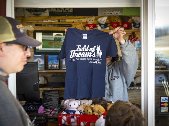 "A vendor at the field charges for souvenirs but visiting the site and playing on the field is free for tourists. David Seidman and his son Lincoln from Highland Park, Ill., look at t-shirts at the gift stand, this one with the famous quote"" Hey dad, wanna have a catch?"""