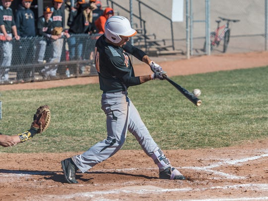 Aztec's Derek Baca connects on a pitch against Kirtland Central on Saturday in Aztec.