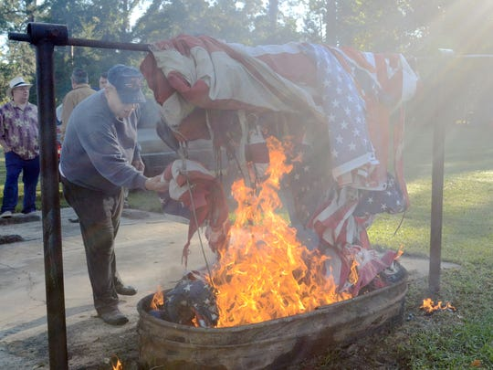 Harold Teal, adjutant of George Simmons Jr. American Legion Post 3, places retired flags in a fire during a flag retirement ceremony held Saturday.