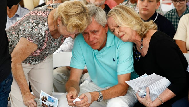 Carl Hiaasen, center, brother of Rob Hiaasen, one of the journalists killed in the shooting at The Capital Gazette newspaper offices, is consoled by his sister Judy, right, and Rob Hiaasen's widow, Maria, during a memorial service Monday, July 2, 2018, in Owings Mills, Md.