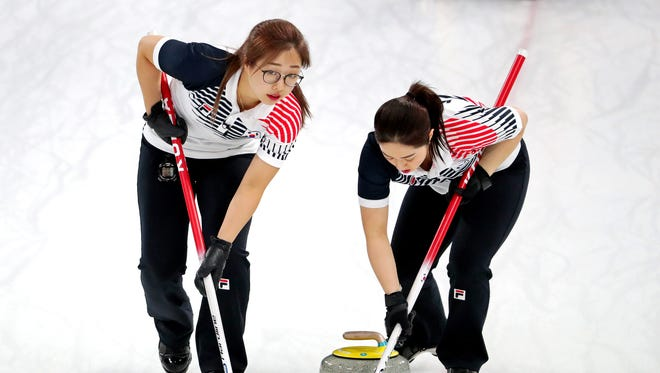 Kim Eun-jung and Kim Seon-yeong sweep in the women's curling gold medal match during the Pyeongchang 2018 Olympic Winter Games at Gangneung Curling Centre.