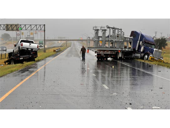 A jackknifed 18-wheeler and a trailer rest on both