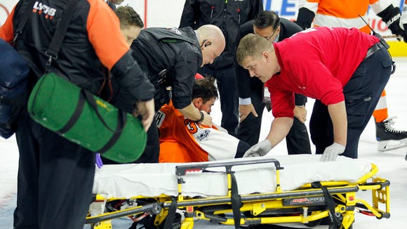 Philadelphia Flyers goalie Michal Neuvirth receives medical attention after apparently collapsing during the first period Saturday.