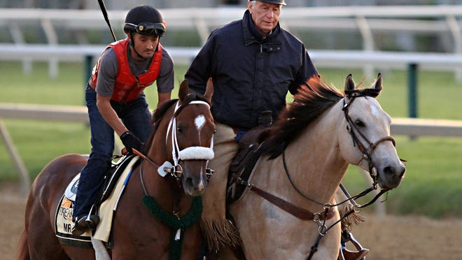 Mr. Z, ridden by exercise rider Edvin Vargas, trots along trainer D. Wayne Lukas as the Preakness Stakes entrant goes to the track for a workout at Pimlico Race Course in Baltimore on Thursday.