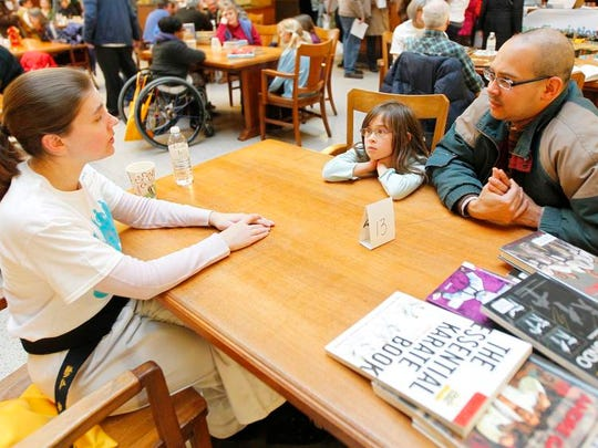 Chelsea Marsh, left, who stands just 5 feet tall, talks about becoming a black belt in martial arts with Carl Almer and his daughter, Beatrix Almer Martin, 8, all of Rochester.