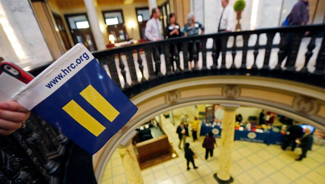 Felicia Brown-Williams, director of public policy for Planned Parenthood Southeast Advocates holds a Human Rights Campaign flag over the rotunda at the Capitol in Jackson, Miss., on March 23, 2016.