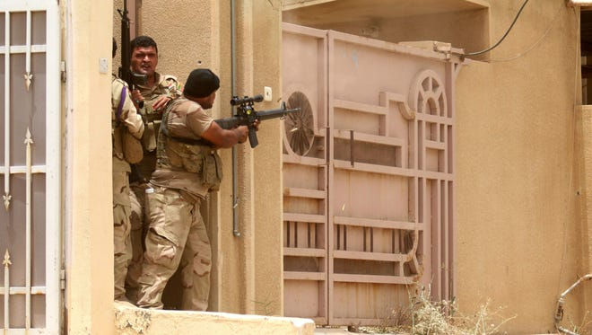 Iraqi pro-government forces take cover in the eastern Askari neighborhood of Fallujah, Iraq on June 19, 2016.