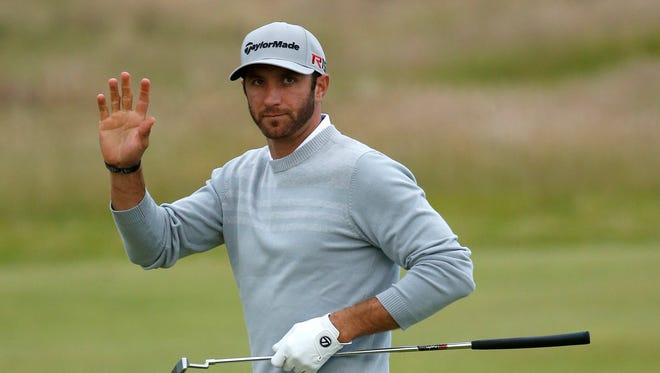 Dustin Johnson waves after making a putt on the 10th green Friday.
