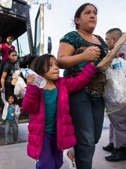 Migrants get off a bus after Immigration and Customs