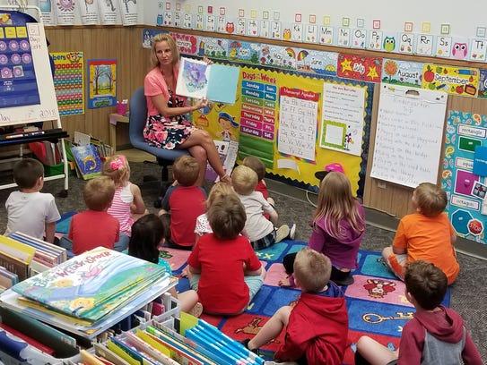 Teacher Tina Forsyth reads as students listen attentively
