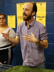 Indianapolis artist Stefan Eicher tells passers-by about plans to break a world record in Tarkington Park for most sparklers lit at one time. Eicher attended a Great Places 2020 unveiling event Tuesday, May 10, 2016, at James Whitcomb Riley School 43 in Indianapolis.