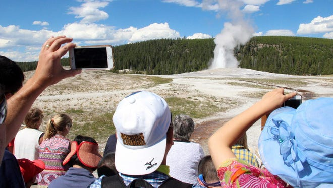 Visitors watch and take photographs as Old Faithful geyser erupts at Yellowstone National Park. Yellowstone is unique in that it features approximately half of the world's geysers.