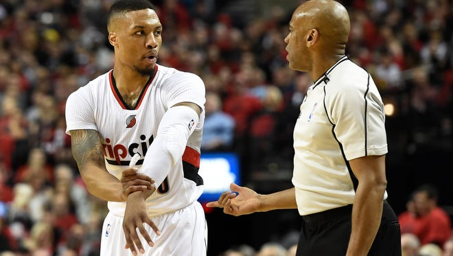 Portland Trail Blazers guard Damian Lillard (0) has some words with referee Tre Maddox (73) during the first quarter of an NBA basketball game against the Denver Nuggets in Portland, Ore., Wednesday, April 13, 2016.