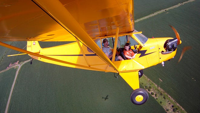 Father and son snap a high-flying selfie over Northern Virginia using a GoPro action camera attached to the wing of a 1946 Piper Cub.