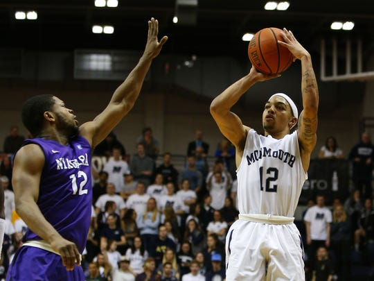 Monmouth  guard Justin Robinson (12) shoots over Niagara's Karonn Davis last season. Robinson needs just 81 points to become the school's all-time leading scorer at the Division I level.