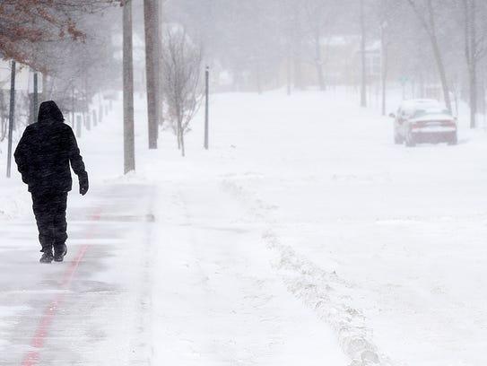 A pedestrian makes his way along Fifth Avenue SE through