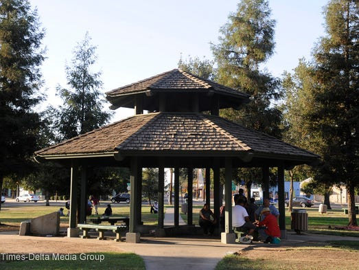 People gather under the shade of the gazebo at Oval Park to play cards on July 10. Some say the Lincoln Oval has improved while others say it's still the same. Regardless, a big rock concert is scheduled Aug. 29 there featuring guitar greats Peter Frampton and Buddy Guy.