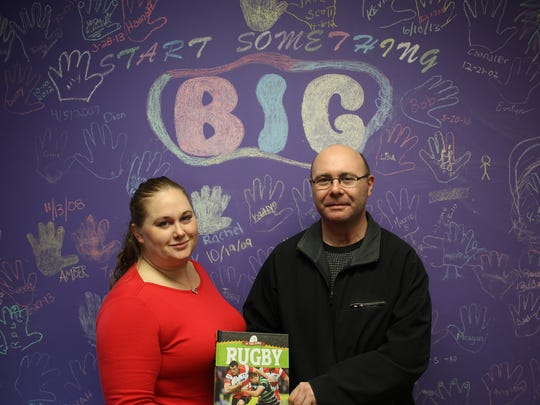 Benjamin Blanc, Vice President of Fond du Lac Rugby, Inc. with Senior Match Support Specialist Jennifer Smith at Big Brothers, Big Sisters of Fond du Lac County, accepting a Rugby book for their library.