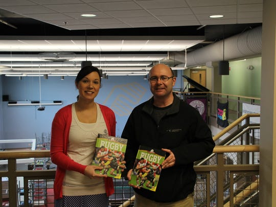 Benjamin Blanc, vice president of Fond du Lac Rugby, Inc with Pam Sippel, Johnsonville club unit director of the Boys and Girls Club of Fond du Lac accepting two books for the club.