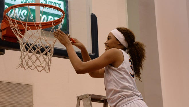COS sophomore guard Idalis Rubalcava cuts down a piece of the net after the Giants' win over Fresno City on Saturday at Porter Field House. The Giants captured an outright Central Valley Conference championship.