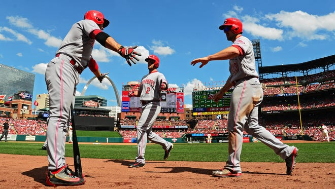 Reds shortstop Zack Cozart (2) is congratulated by first baseman Joey Votto (left) after scoring on a sacrifice fly by left fielder Adam Duvall (23) against the Cardinals in the sixth inning.