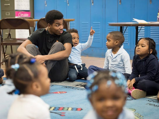 Ricardo Carter works with Aiton Elementary School students
