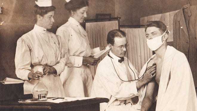 Dr. F. E. Jackson examines a patient at the City Dispensary as nurses from the tuberculosis clinic visit to assist.