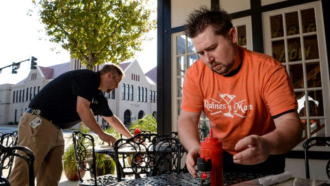 General Manager Travis Kernels, left, and Silas Eanes, right, a server at Raines on Main Bar and Grill, set up tables for lunch for the new restaurant at 312 South Main Street in downtown Anderson on Thursday.