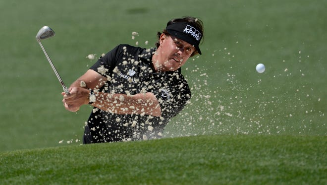 Phil Mickelson hits out of a bunker on the 2nd hole during the first round of the 2014 The Masters golf tournament at Augusta National Golf Club.