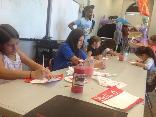 "Kayleigh Gordon (front, left), 9, joins fellow campers in painting ""Hello, my name is"" tags Monday to kick off a week of graffiti art at the Alexandria Museum of Art's first session of summer art camp."