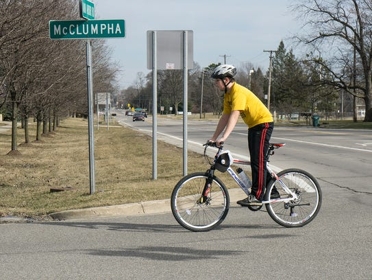 A bicyclist crosses the intersection of Ann Arbor Road