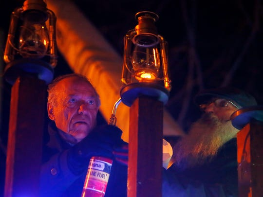 The annual Menorah lighting on the Morristown Green.  Norman Feinstein, Principal, Vice Chairman, Fund Manager of The Hampshire, lights the second lamp of Chanukah on the Green as Reuven Tarlow, a building engineer from the Rabbinical College of America looks on. December 13, 2017. Morristown, New Jersey