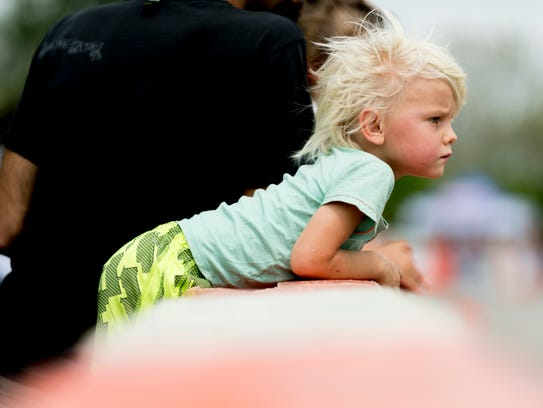 Shane Paul, 4, watches vintage cars race with his parents,
