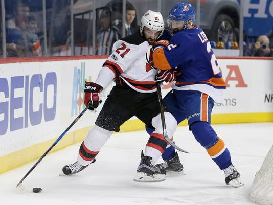 New Jersey Devils' Kyle Palmieri (21) and New York Islanders' Nick Leddy (2) fight for control of the puck during the first period of an NHL hockey game Friday, March 31, 2017, in New York. (AP Photo/Frank Franklin II)