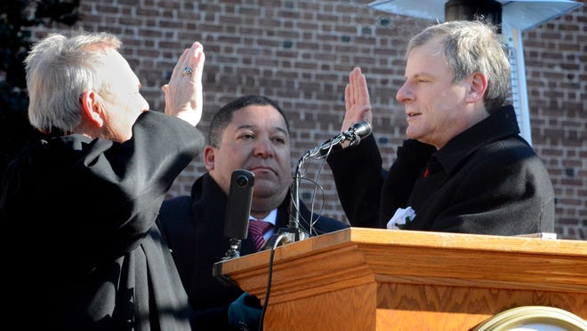 Recently retired judge Stephen Linebaugh administers the oath of office to York City Mayor Michael Helfrich with Latino leader Lou Rivera standing by during a ceremony outside city hall Tuesday, Jan 2, 2017. Helfrich is the 25th mayor of York. Bill Kalina photo